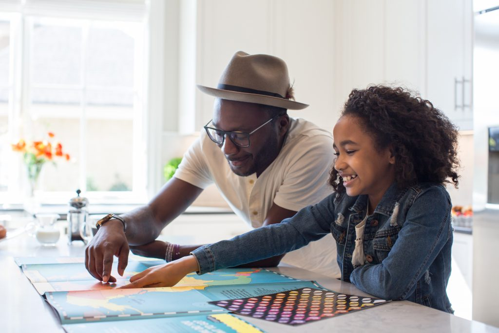 A preteen girl and her father smile as they point to a country on a colorful map. They are stood in a bright and airy white kitchen. Recognizing that God's promises cover all our needs, helps us to relax and enjoy life to the fullest.