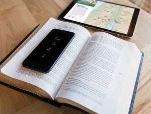 Pictured is a copy of the Filament Bible, sat open on a table with a mobile phone showing the accompanying app, and a tablet also showing the app.