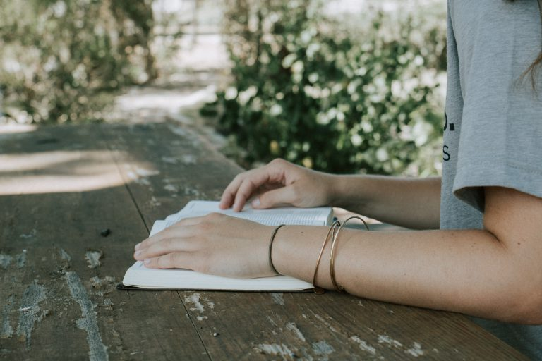 A young woman with bangles on her right wrist, sits at a wooden table in a yard reading her Bible. Want to know where to start reading the Bible? Start with the Gospel of John!