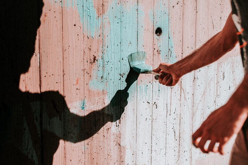A man paints a red fence with a new blue color. One of the ways in which we can connect with others and build trusting relationships is by serving, or helping, them in a practical way.