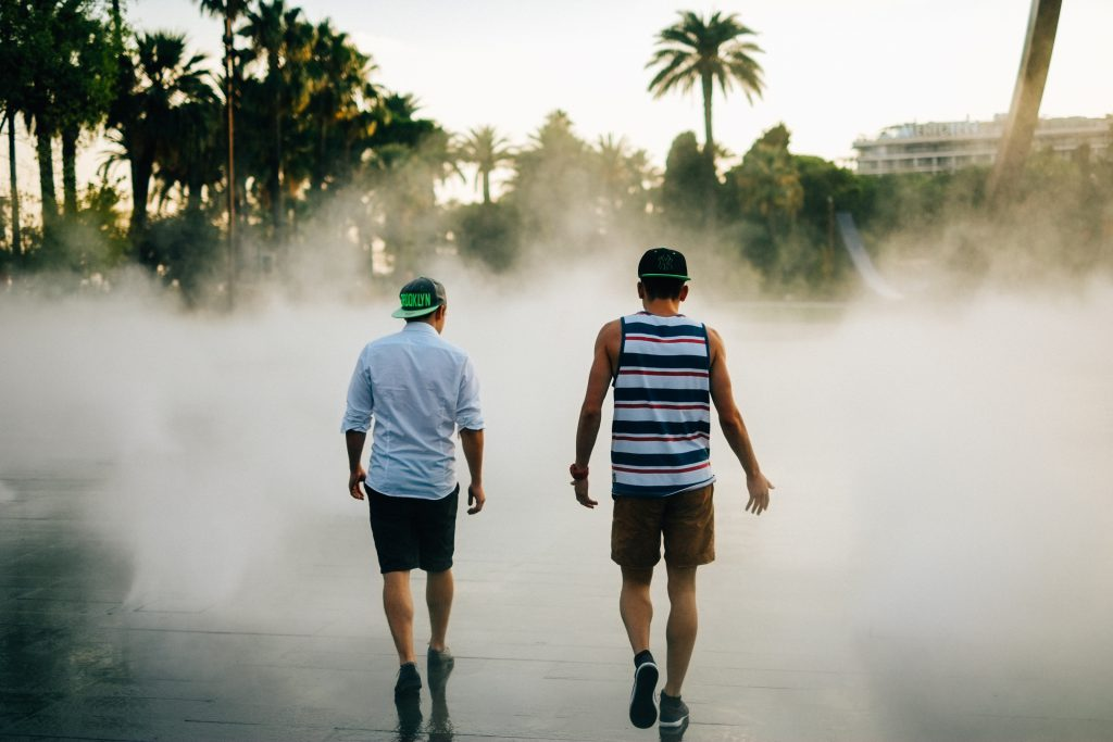Talking about solutions is the final part of establishing trust and friendship with someone who is different to us. Finding a solution to a common problem is the greatest blessing we can enjoy from having a trusted relationship with someone different to us. In this photo, two young men in shorts and shirts, with backwards baseball caps, walk on slick concrete with what appears to be smoke obscuring the view of palm trees ahead of them. They are talking, with one of the men gesturing as he speaks.