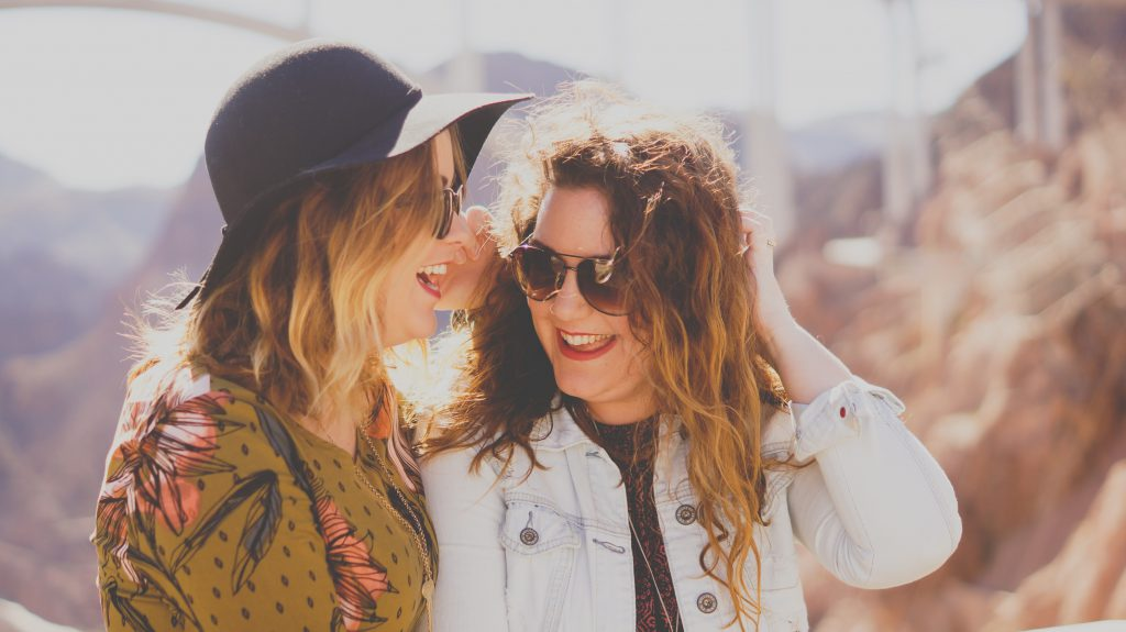 Two fashionable young ladies stand close together outside in the sunshine. They both wear sunglasses and are laughing. To help a friend along on their faith journey, you can invite them to attend your small group, or share your story with them.