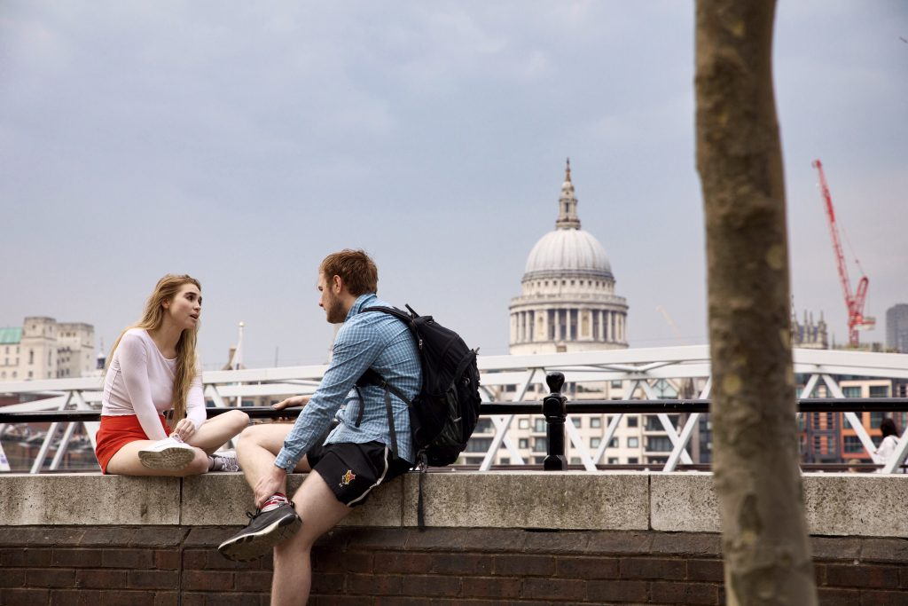 A young couple sit opposite each other on a wall by the River Thames in London. Teh sky behind them looks cloudy, but they both wear shorts and long-sleeve tops. We all have an opportunity to share Jesus with others, all it takes to start is a friendly conversation!